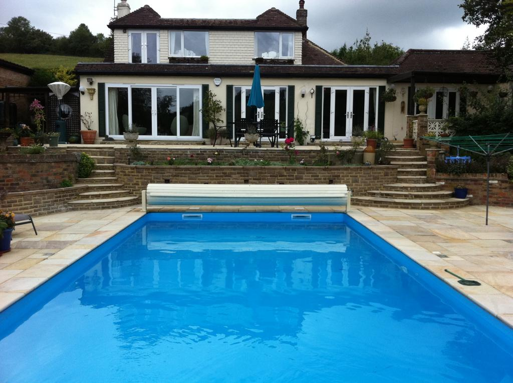 Outdoor swimming pool and patio showing view of house